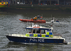 © Licensed to London News Pictures. 16/01/2013. London, UK Police and RNLI boats search the Themaes after the incident. A damaged crane is seen hanging from the side of the St George's Wharf development near Vauxhall in in London today (16/01/13) after a being hit by a helicopter, which then crashed.  Photo credit : Stephen Simpson/LNP