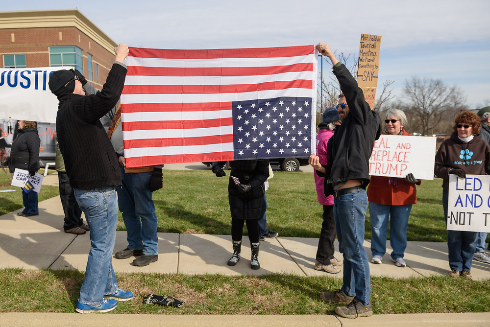 An American flag is held upside down, a sign of distress. Groups protest The Republican Party's proposed changes to the Affordable Care Act during a visit by Vice President Mike Pence with Kentucky Governor Matt Bevin and business leaders Saturday, March 11, 2017 at Trane Parts and Distribution Center, 12850 Plantside Drive, Louisville, Ky. (Photo by Brian Bohannon)