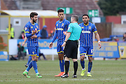 George Francomb of AFC Wimbledon, Lyle Taylor of AFC Wimbledon & Andy Barcham of AFC Wimbledon quiz the referee during AFC Wimbledon and York City at the Cherry Red Records Stadium, Kingston, England on 19 March 2016. Photo by Stuart Butcher.