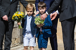Windsor, UK. 21st April 2019. Local schoolchildren arrive to give traditional posies of flowers to the Queen as she leaves the Easter Sunday service at St George's Chapel in Windsor Castle.