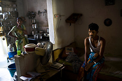 Sandeep T. sits on his bed in his apartment in a large apartment building in Mumbai, India. Sandeep is currently undergoing TB treatment and is slowly beginning to feel better.  He had been bed ridden for several weeks while his aunt, standing in the kitchen, took care of him.