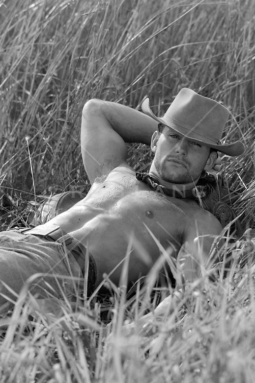 sexy shirtless cowboy in a field with tall grass
