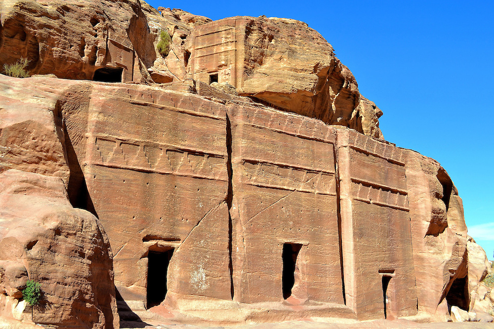 Three Double Pylon Tombs Along Street of Fa&ccedil;ades in Petra, Jordan <br /> There are eight designs of tombs in Nabataean architecture. They are distinguished by the complexity of their carvings and whether they have columns, pediments or arches. The pattern on these three tombs along the Street of Facades is called Double Pylon. This monument type averages 17 feet across but can measure up to 50 feet wide. Notice their two rows of the crowstep motif.  Over 80% of the burial monuments at Petra have some variation of this geometrical design.