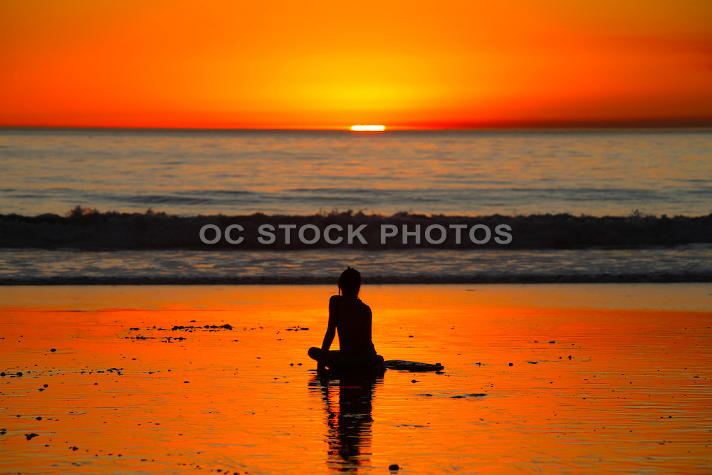 Girl Sitting on the Beach at Sunset