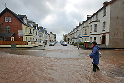 © Licensed to London News Pictures. 03/02/2014. Exmouth, UK. A woman walks throughout floodwater. Seawater floods the seafront in Exmouth Devon.The water breached defences and flooded Morton Road, St Andrews Roads, Victoria Road and some of the other surrounding streets. Police closed the road to vehicles. Officials were seen delivering sandbags to the local residents. . Photo credit : Russ Nolan/LNP