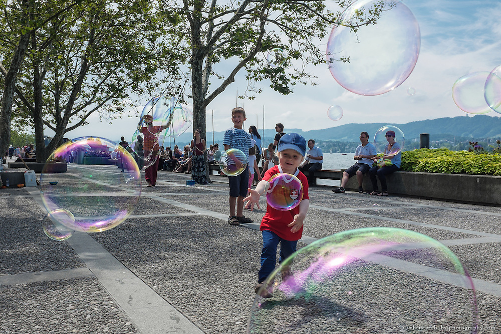 Children play with huge soap bubbles which are blown up by a street artist at Lake Zurich´s promenade in Zürich City.