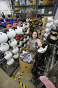 Christina Merritt of Lorain works on removing the wrapping from football helmets after they come out of the paint shop at sports equipment manufacturer Riddell in Elyria, Ohio on July 29, 2009.