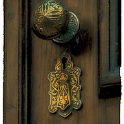Decorative and functional brass door handle and key lock on front  door entrance of brownstone.