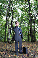 Portrait of business man in forest talking on mobile phone