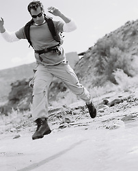 Hiker jumping over water in the desert