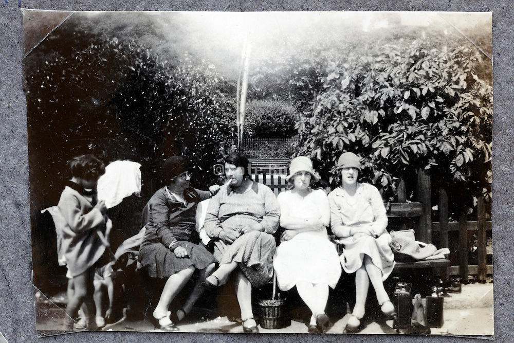 an all female group relaxing and smoking on a bench 1900s England