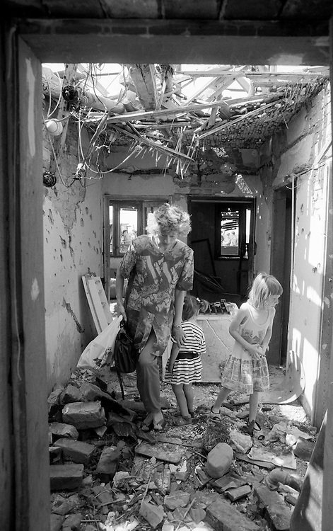 A mother and her children walk through their war destroyed home located along the front lines in Ivanovac, Croatia.