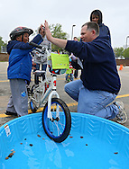 """Kahmarrus Jones (from left) of Cedar Rapids high fives Kaplan University adjunct professor Joe Schmitz of Atkins after completing the RAGBRAI themed course and dipping his front tire in the """"river"""" during the 2nd Annual Bike Rodeo at Kaplan University, 3165 Edgewood Parkway, in Cedar Rapids on Saturday morning, April 28, 2012. Activities included a safety talk from the Cedar Rapids Fire Department and Cedar Rapids Police Department, bike adjustments, a bike helmet giveaway, RAGBRAI themed course, and bike giveaway drawing. (Stephen Mally/Freelance)"""