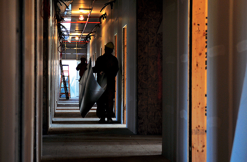 Ambient light shines from open doorways as construction workers carry materials inside West Village, Wednesday, Nov.28. The project of new student housing is expected to be completed in Fall 2008.