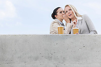 Low angle view of businesswoman whispering in coworker's ear while standing on terrace against sky
