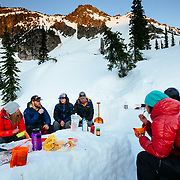 The team eating dinner as the sunsets over basecamp in Glacier National Park.