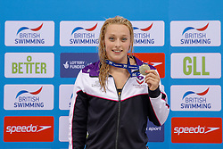 Rachael Kelly of Loughbrough University celebrates on the podium after winning the Womens 100m Butterfly Final - Photo mandatory by-line: Rogan Thomson/JMP - 07966 386802 - 16/04/2015 - SPORT - SWIMMING - The London Aquatics Centre, England - Day 4 - British Swimming Championships 2015.