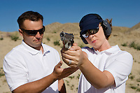 Instructor assisting woman aiming hand gun at firing range in desert