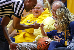 Dec 8, 2018; Morgantown, WV, USA; A West Virginia Mountaineers fan fist bumps an official during the second half against the Pittsburgh Panthers at WVU Coliseum. Mandatory Credit: Ben Queen-USA TODAY Sports