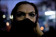 """Kate, age 30, transvestite from 17 years, after a performance lasted the whole night at a wedding party. Early morning in Lahore, Pakistan on Wednesday, December 03 2008.....""""Not men nor women"""". Just Hijira, Kusra. Painted lips, Kajal surrounding their eyes and colourful veils..Pakistan is today considered a strongly, foundamentalist as well, islamic country. But under its reputation, above all over the talebans' continuos advancing, stirs a completely extraneous world, a multiethnic mixed society. Transvestites make part of it, despite this would not be admitted by a strict law. Third gender, the Hijira are born as men (often ermaphrodites) or with an ambiguous genital situation, and they have their testicles and penis removed through a - often brutal - surgical operation. The peculiarity is that this operation does not contemplate the reconstruction of a female organ. This is the reason why they are not considered as men nor women, just Hijira. They are often discriminated, persecuted  and taxed with being men prostitutes in the muslim areas. The members of this chast perform dances during celebrations, especially during weddings, since it is anciently believed that an EUNUCO's dance and kiss in the wedding day brings good luck to the couple's fertility...To protect the identities of the recorded subjects names and specific .places are fictionals."""