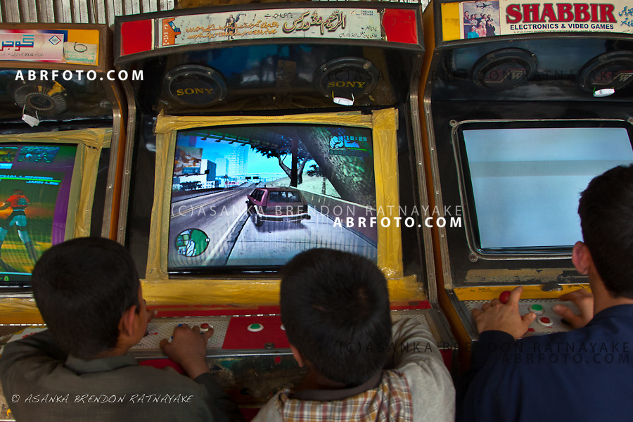 Young Afghan boys playing the American video game 'Grand Theft Auto' at a video game arcade in Jalalabad, Afghanistan