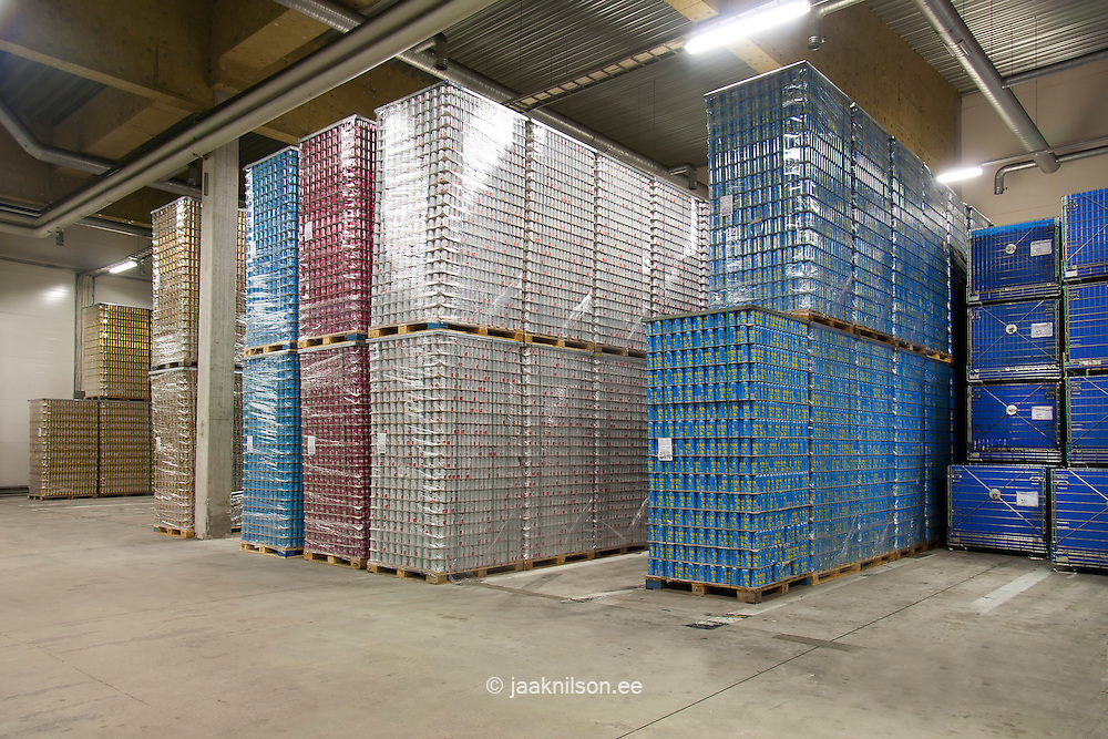 Warehouse, stacks of wrapped cans, boxes and crates of beer and drinks.