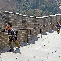Asia, China, Badaling. Two boys race to climb a section of the Great wall.