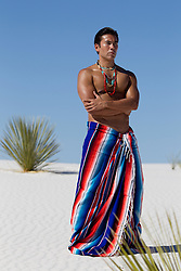 Asian American man wrapped in an indian blanket in White Sands, New Mexico desert