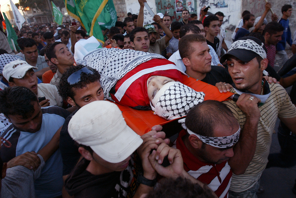Palestinians carry the bodies of an 18 years old teenager killed during clashes in the West Bank village of Naalin on August 4 2008. Photo by Olivier Fitoussi