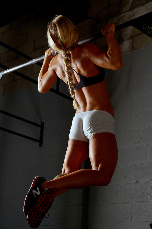 Woman doing pull-ups in a gym in San Diego, CA