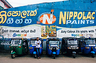 A man leans against his tuk tuk waiting for customers, Hapatule, Sri Lanka, Asia