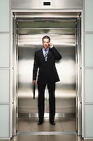 Businessman Using Cell Phone on Elevator front view