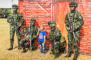 "11 JANUARY 2014 - BANGKOK, THAILAND: A Thai boy poses for photos with Thai special forces soldiers during an Army open house on Children's Day. The Royal Thai Army hosted a ""Children's Day"" event at the 2nd Cavalry King's Guard Division base in Bangkok. Children had an opportunity to look at military weapons, climb around on tanks, artillery pieces and helicopters and look at battlefield medical facilities. The Children's Day fair comes amidst political strife and concerns of a possible coup in Thailand. Earlier in the week, the Thai army announced that movements of armored vehicles through Bangkok were not in preparation of a coup, but were moving equipment into position for Children's Day.      PHOTO BY JACK KURTZ"