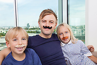 Portrait of mid adult man and children with artificial mustache at home