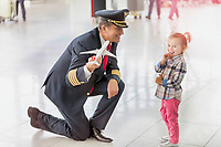 Portrait of mature pilot holding airplane toy while playing with cute little girl in airport