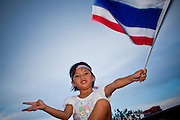"Apr. 18, 2010 - Bangkok, Thailand: A child waves the Thai flag from the roof of her family's minivan during a peace protest in Bangkok Sunday. Thousands of so called ""Pink Shirts"" jammed the area around Victory Monument in Bangkok to show support the Thai Monarch, King Bhumibol Adulyadej, and against the Red Shirts, who are demonstrating just a few kilometres away in the Ratchaprasong area. The Pink Shirts claim to not support either of the other political factions who wear colors - the Red Shirts, who support deposed Prime Minister Thaksin Shinawatra and their opponents the Yellow Shirts, who are against Thaksin.   Photo By Jack Kurtz"