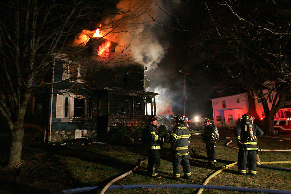 Westwood, MA 03/31/2011.Firefighters from Westwood and surrounding towns work to control a house fire on Washington St. at Dean early Thursday morning.  The 3 alarm fire started on the front porch and quickly spread through all three floors and the roof, officials said..Alex Jones / www.alexjonesphoto.com