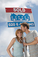 Couple holding sold sign against sky man kissing woman
