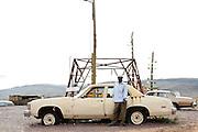 198 / The Hills have Eyes: AFRIKA, MAR, MAROKKO, OUARZAZATE, OUARZAZATE, 24.09.2010: Ein Mann lehnt sich auf ein Autowrack an. Das Gelaende und die verlassene Tankstelle wurden als Filmkulisse fuer den Film The Hills Have Eyes benutzt. In Ouarzazate befinden sich die groessten Fimstudios Marokkos. - Marco del Pra / imagetrust - Stichworte: Afrika, alt, Atlas, Auto, Autowrack, Benzin, Diesel, Drehort, Film, Filmkulisse, Filmstudio, kaputt, Koenig, Koenigreich, Kulisse, Mann, MAR, Marokko, Model Release:No, mohammed VI, OUARZAZATE, Property Release:No, Reifen, Sand, Stichwort, Tank, Tanken, Tankstelle, The Hills have Eyes, Verlassen, verwuestet, Wueste, zerstoert, Wrack, Karrosserie, Chevrolet, ,Property Release:No, Stichwort,