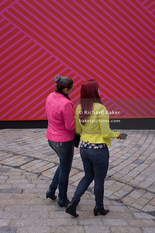 Girls and pink background of main venue for London Fashion Week at Somerset House.