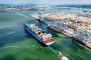 Nederland, Zuid-Holland, Rotterdam, 10-06-2015; Container Ship Morten van Maersk Line verlaat de APM terminal aan de Europahaven op de Maasvlakte. Het schip is onderweg naar open zee en wordt geassisteerd door twee sleepboten van Iskes.<br /> Containership Morten Maersk Line leaves the APM terminal at the Europe harbour on the Maasvlakte. The ship is on its way to open sea and is assisted by two tugs from Iskes.<br /> <br /> luchtfoto (toeslag op standard tarieven);<br /> aerial photo (additional fee required);<br /> copyright foto/photo Siebe Swart