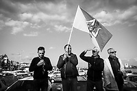 ACI TREZZA, ITALY - 28 OCTOBER 2017: Supporters of the  Five Star Movement (Italian: Movimento 5 Stelle, or M5S) candidate Giancarlo Cancelleri, running for governor of Sicily in the upcoming Sicilan regional election, hold a Sicilian flag as they wait the arrival of the candidate and the M5S leader Beppe Grillo here in Aci Trezza, Italy, on October 28th 2017. <br /> <br /> The M5S organised a march from Aci Trezza to Catania (6 miles), where a rally will be held in the evening.<br /> <br />  The Sicilian regional election for the renewal of the Sicilian Regional Assembly and the election of the President of Sicily will be held on 5th November 2017.