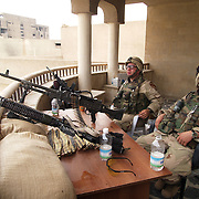29 April 2004....Baghdad, Iraq.....US troops in Sadr city.....Troops from 2 Cav have the responsibility for patroling the streets of Baghdads most violent nieghbourhood, Sadr city...The residents are amoung Baghdads poorest with a high level of unemployment, the firebrand cleric Moqtada al Sadr has great support in this area and it has recently been the scene of violent clashes. His followers took over several buildings and the US forces have fought to regain control...The soldiers report that they are attacked nightly with riflefire, rocket propelled grenades and mortars.......Specialist Rodney Hudson (right) and Private Juan Martinez take an oppurtunity to relax during the last few quiet hours of daylight whilst on guard at one of the building they retook fom local militias. When darkness falls they can expect an attack at any time.....