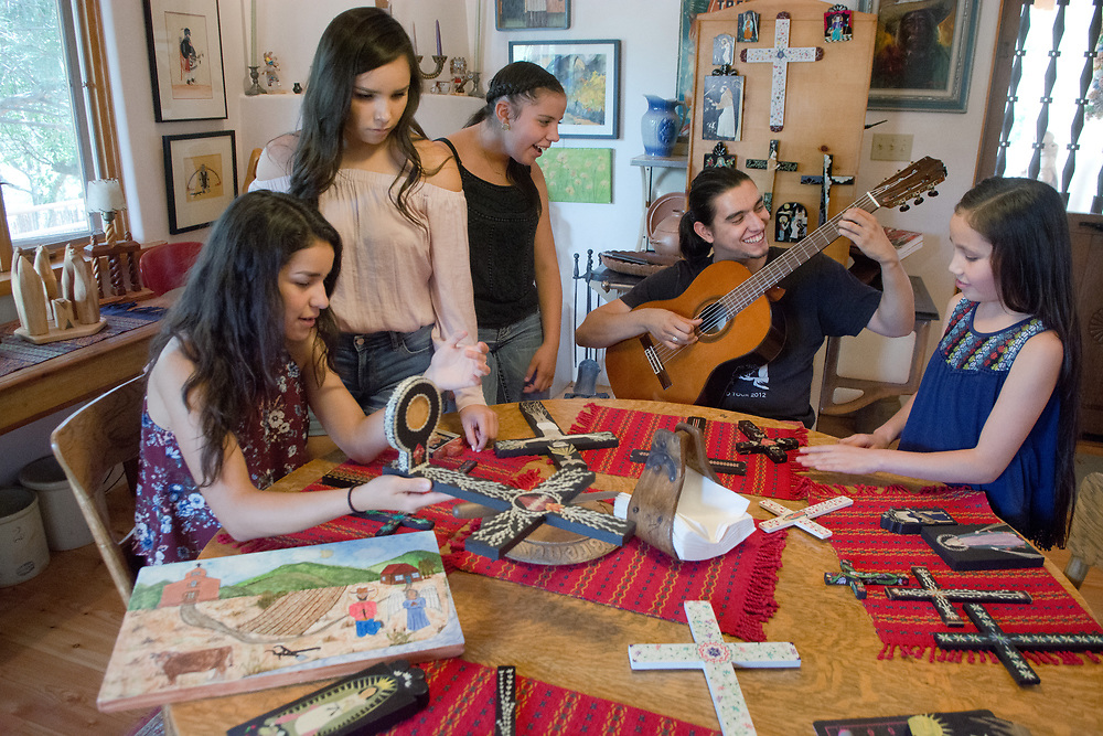 mkb072517e/North/Marla Brose --  Diana Moya-Lujan's grandchildren gather around the kitchen table looking at their straw applique artwork during a studio tour at Moya-Lujan's Santa Fe home, Tuesday, July 25, 2017. From left is Andrea Torres, Madison Lujan-Davis, Emma Lujan-Davis, Isaiah Martinez and Hannah Lujan-Davis. Moya-Lujan will be showing work at Spanish Market along with her daughter and four granddaughters. (Marla Brose/Albuquerque Journal)