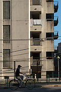 A Japanese woman rides a bicycle in front of an old apartment building near Shinjuku, Tokyo, Japan. Friday July 10th 2015