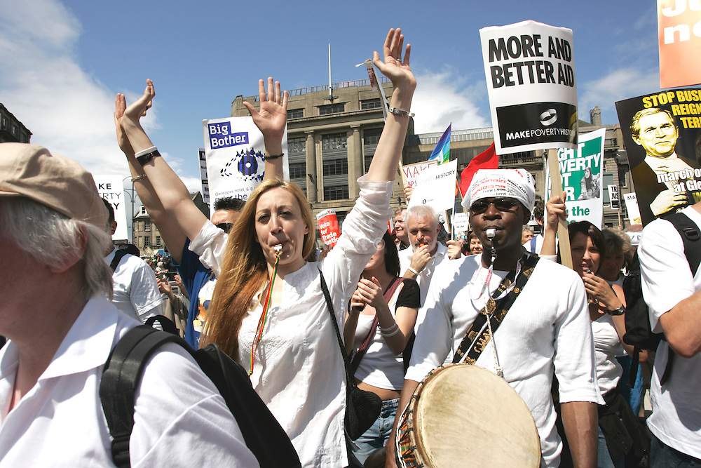 MAKE POVERTY HISTORY RALLY EDINBURGH.Demonstrators blow the whistle on world poverty..Picture taken on the 2nd July and published in the New Statesman 11th July The biggest ever anti-poverty movement came together under the banner of MAKEPOVERTYHISTORY in 2005 calling for urgent action for more and better aid, debt cancellation and trade justice.<br /> Millions of people wore white bands, 444,000 people emailed the Prime Minister about poverty and 225,000 took to the streets of Edinburgh for the Make Poverty History march and rally.<br /> The campaign ensured that global poverty was placed higher on the national and global agenda than ever before.