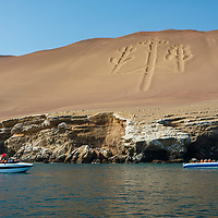 Tourist boats in front of the Paracas Candelabra, or the Candelabra of the Andes, a well-known prehistoric geoglyph found on the northern face of the Paracas Peninsula at Pisco Bay in Peru.