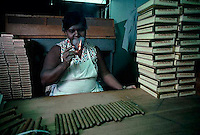 December 1981, Havana, Cuba --- A cigar maker at the Montecristo factory lights up a cigar to smoke as she works. --- Image by © Owen Franken/CORBIS