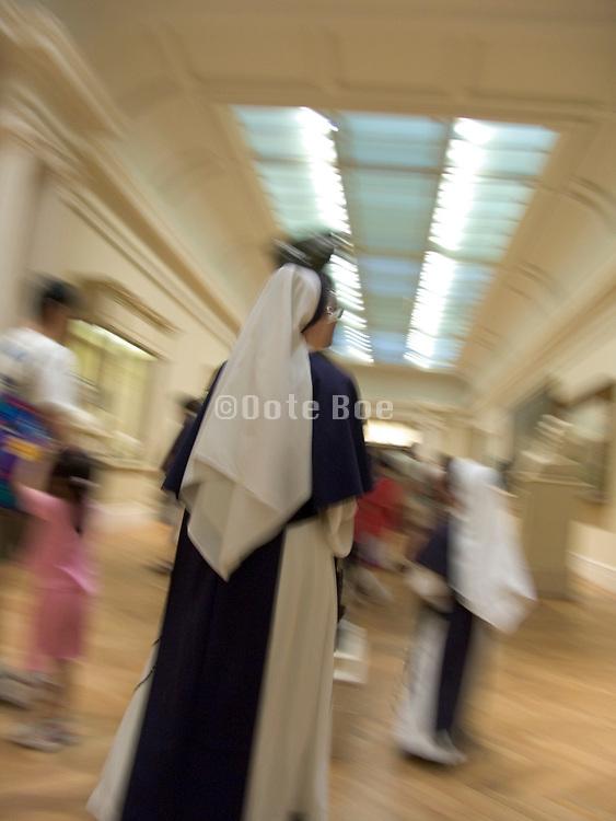 nuns and guests walking through a hall