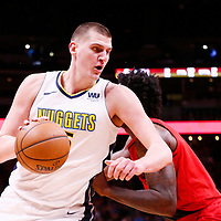 09 April 2018: Denver Nuggets center Nikola Jokic (15) drives past Portland Trail Blazers forward Al-Farouq Aminu (8) during the Denver Nuggets 88-82 victory over the Portland Trail Blazers, at the Pepsi Center, Denver, Colorado, USA.